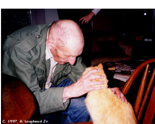 [photo image: Beat writer William S. Burroughs photographed at home with cat Ginger, April 1997, Lawrence, KS. Copyright 1997, G. Laughead]